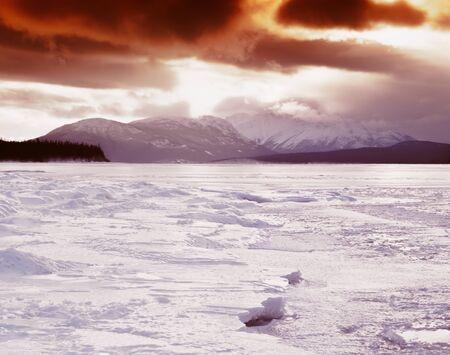 yukon territory: Winter landscape of frozen Tagish Lake, Yukon Territory, Canada, blizzard storm clouds illuminated by low midwinter sun