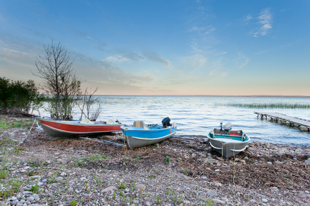 Colorful motorboats on shore of calm water of Lesser Slave Lake in Hillards Bay Provincial Park in northern Alberta, Canada
