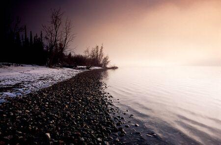 yukon territory: Eerie early winter landscape scenery fog mists over calm water surface of Tagish Lake, Yukon Territory, Canada Stock Photo