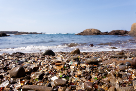 Pile of rounded glass shards or seaglass on Pacific Ocean gravel beach of Fort Bragg, California, US