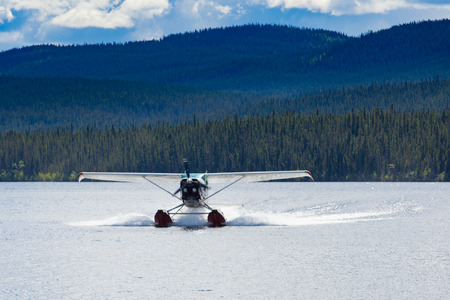 Float plane landing on remote wilderness lake in boreal forest taiga of Yukon Territory, Canada