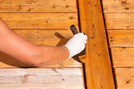 staining: Painter staining deck boards with transparent protective outdoor decking paint applying stain with brush