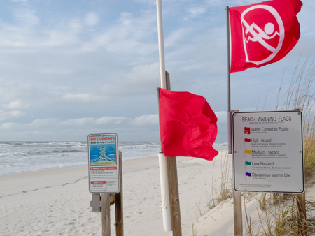 explanatory: Red flags and explanatory signs signal Water closed to public and prohibit swimming in ocean due to dangerous surf, undercurrent and storm conditions