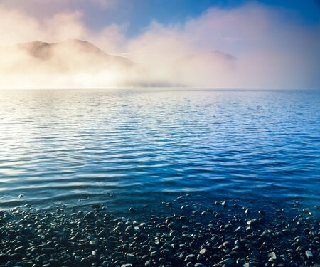 tranquil: Landscape scenery morning fog mists over blue water surface of Tagish Lake, Yukon Territory, Canada