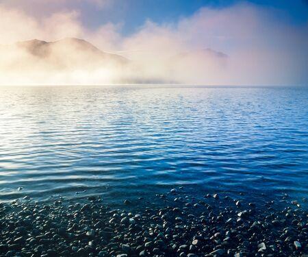 yukon territory: Landscape scenery morning fog mists over blue water surface of Tagish Lake, Yukon Territory, Canada