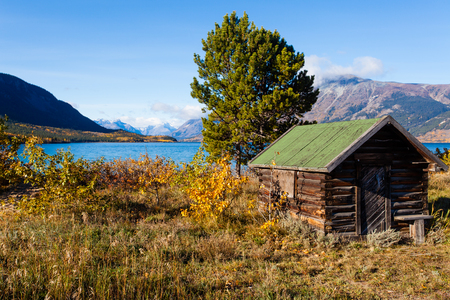 Pristine wilderness Landscape with historic wooden log building at shore of Lake Bennett near Carcross, Yukon Territory, Canada Stock Photo