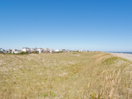 hatteras: Vacation homes village behind low sand dunes and sandy beach on Hatteras Island of Outer Banks, OBX, North Carolina, NC, US