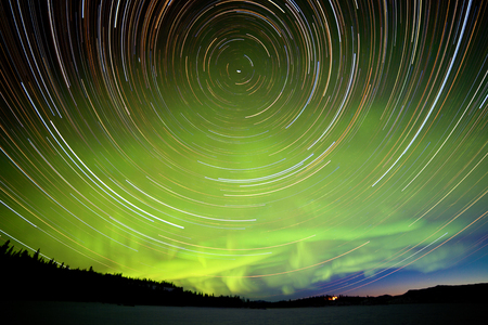 Astrophotography star trails with green glowing display of Northern Lights or Aurora borealis at crack of dawn in Yukon Territory, Canada Stock Photo