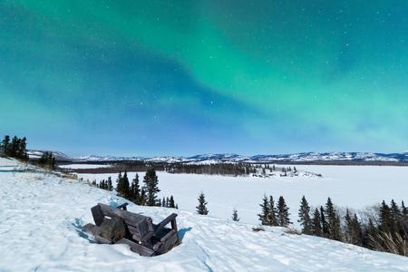 yukon territory: Northern Lights or Aurora borealis or polar lights forming green swirls over snowy bench in moon lit night overlooking winter landscape of Lake Laberge, Yukon Territory, Canada