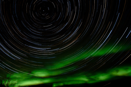 Astrophotography star trails with green glowing display of Northern Lights or Aurora borealis in Yukon Territory, Canada