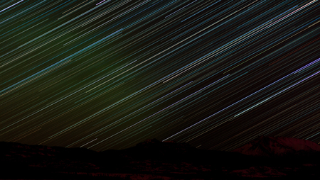Astrophotography star trails over hills and boreal forest or taiga of Yukon Territory, Canada Imagens