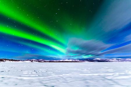 Spectaculaire weergave van intens noorderlicht of Aurora borealis of polaire lichten die groene wervelingen vormen boven besneeuwd winterlandschap