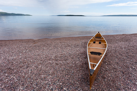 beached: Canoe beached on gravel shore of calm Lake Superior water wilderness of Ontario, ON, Canada, ready for an adventure trip outdoors