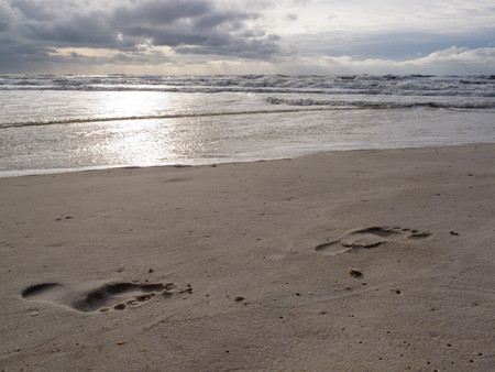 Human bare foot prints in wet sand of beautiful beach with stromy ocean raging in background marking the end of summer, Gulf Coast in Florida, FL, USA