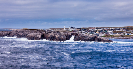 Port-aux-Basques village on Newfoundland, Atlantic Canada, with storm battered barren rocky shore protecting the town Stock Photo
