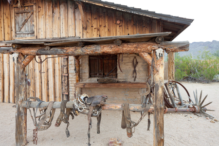 Historic boarded up wooden barn stable facade building with old leather saddle and iron tools near Tucson, Arizona, AZ, USA Stock Photo