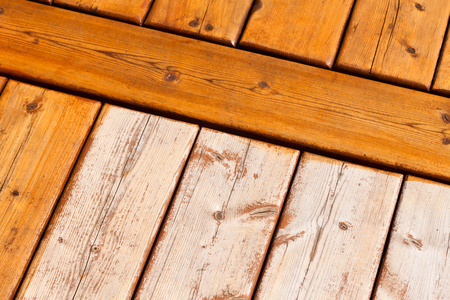 Wooden deck boards partially finished with transparent protective outdoor decking paint stain and partially unfinished weathered raw wood surface