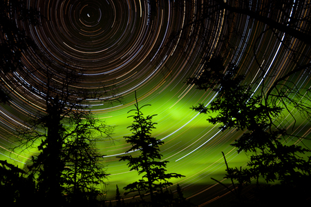 yukon territory: Astrophotography star trails with green glowing display of Northern Lights or Aurora borealis over boreal forest or taiga of Yukon Territory, Canada