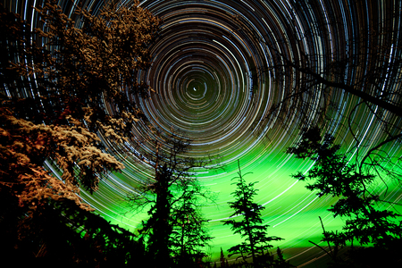 Astrophotography star trails with green glowing display of Northern Lights or Aurora borealis over boreal forest or taiga of Yukon Territory, Canada