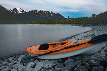 Kayak ready to go beached on rocky shore of Windy Arm of Tagish Lake, Yukon Territory, Canada