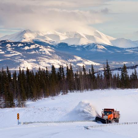除雪機の雪嵐ブリザード ユーコン準州、カナダの美しい農村冬景色の後に道路をクリア