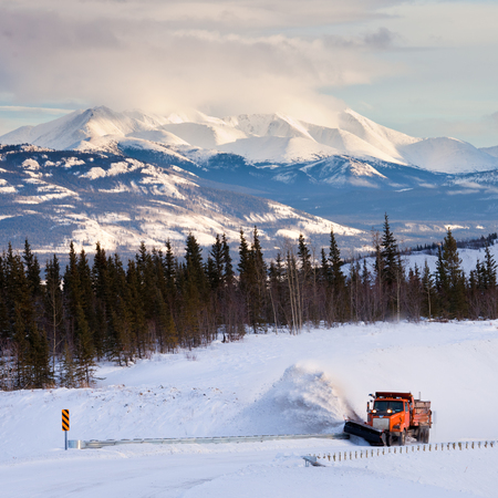 Snow plow clearing road after snow storm blizzard in beautiful rural cold winter landscape of Yukon Territory, Canada