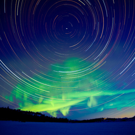 Astrophotography star trails at crack of dawn with green glowing display of Northern Lights or Aurora borealis in Yukon Territory, Canada Stock Photo