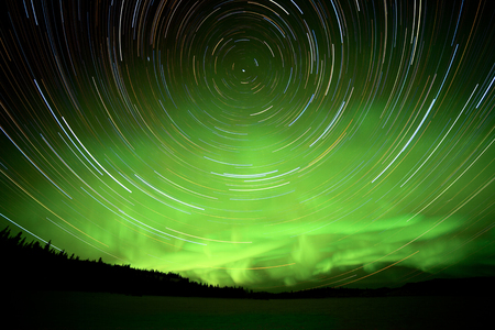 yukon territory: Astrophotography star trails with green glowing display of Northern Lights or Aurora borealis in Yukon Territory, Canada