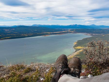 yukon territory: Hiking boots of Hiker resting in alpine tundra overlooking Little Atlin Lake near Tagish, Yukon Territory, Canada