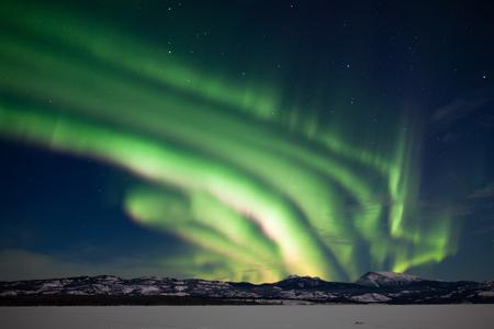 yukon territory: Bright bands of Northern Lights or Aurora borealis or polar lights dancing over moon-lit winter landscape of frozen Lake Laberge, Yukon Territory, Canada Stock Photo