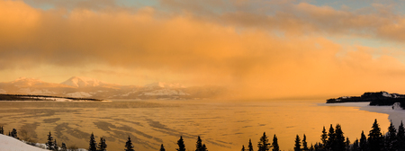 Lake Laberge, Yukon Territory, is about to freeze over while steaming at -30 degrees celsius. Фото со стока