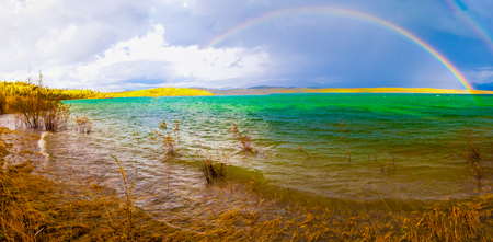 A Thundershower producing a rainbow over the gree-blue waters of pristine Lake Laberge, Yukon Territory, Canada. Stock Photo
