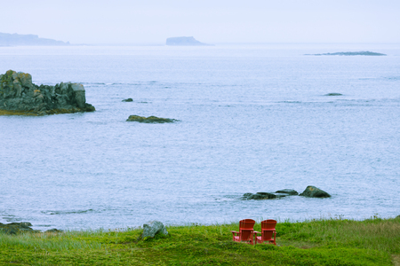 Red wooden Adirondack Chairs in beautiful coastal landscape of Strait of Belle Isle, Newfoundland, NL, Canada