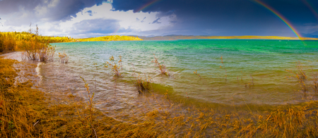A Thundershower producing a rainbow over the gree-blue waters of pristine Lake Laberge, Yukon Territory, Canada