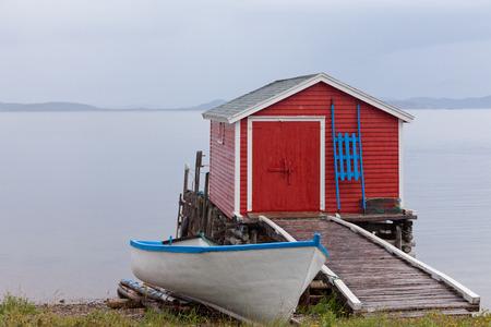 Beautiful red fishing shack and boat house at Newfoundland Atlantic ocean shore, NL, Canada Stock Photo