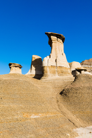 Famous touristic landmark attraction of geologic sedimentary sandsone rock erosion formation called hoodoos in Red Deer River valley near Drumheller, Alberta, AB, Canada