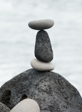 Balanced black lava stones and white pebbles symbolizing stability, zen, harmony, balance and relaxation