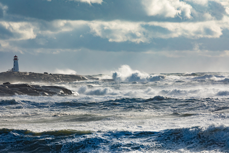 Lighthouse at Peggys Cove high on granite rock cliffs with stormy Atlantic Ocean surf raging, Nova Scotia, Canada