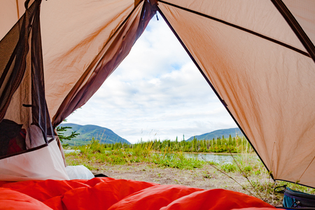 Campsite wilderness nature view of Yukon River, Yukon Territory, YT, Canada, from inside a tent with sleeping bag laid out 写真素材