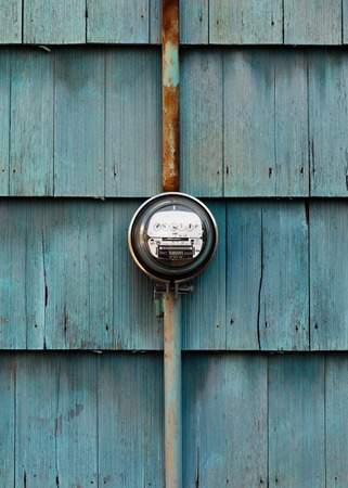 Electricity line drop residential dial power meter mounted on exterior wooden shingle siding wall with faded blue paint