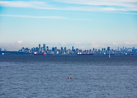 Vancouver City at the Western Canadian Pacific Ocean coast with oil tankers anchored in harbor and Mount Baker in the far distance shadowing the cityscape skyline, Biritish Columbia, BC, Canada 写真素材
