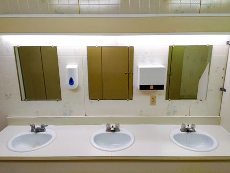 Slightly grungy public washroom row of sinks 写真素材