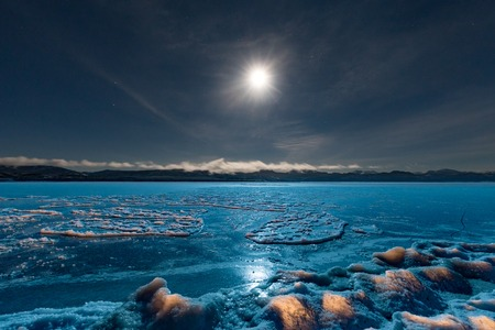 Full moon over frozen Lake Laberge Yukon Canada