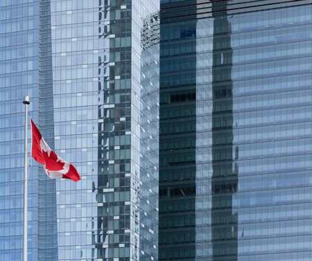 Canadian Maple Leaf flag flying on pole in front of glass facades of high-rise office buildings in downtown Toronto, Ontario, ON, Canada