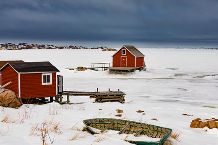 Fishing stage shacks and old wooden skiff row boat at shore of frozen North Atlantic Ocean in outport town of Joe Batts Arm on Fogo Island, Newfoundland, NL, Canada