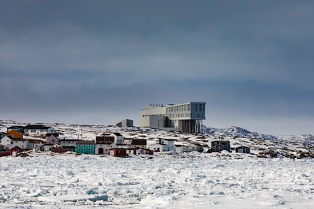 Outport fishing village of Joe Batts Arm with Fogo Inn hotel in frozen coastal winter landscape of Fogo Island, Newfoundland, NL, Canada