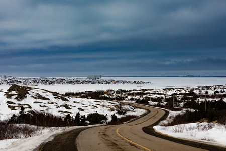 Road from Tilting to Joe Batts Arm, two outport fishing villages at frozen North Atlantic Ocean winter landscape of Fogo Island, Newfoundland, NL, Canada