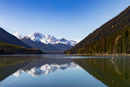 Tall snow-capped mountains surround Duffey Lake Provincial Park with high peaks reflected on calm lake surface, British Columbia, BC, Canada 写真素材