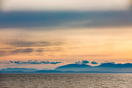 Distant eastern shore of Vancouver Island silhouette of forested hills and mountains veiled by haze, Pacific Ocean Coast of British Columbia, BC, Canada 写真素材