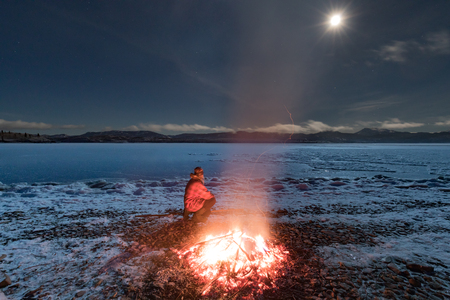 Outdoors person sitting by warming big bonfire looking at full moon shining over blue ice surface of frozen Lake Laberge, Yukon Territory, YT, Canada 写真素材 - 118488116
